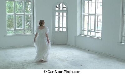 Beautiful girl in white dress whirling in the middle of room, slow motion