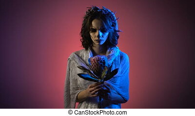 Beautiful girl in white dress with scarry make-up and flower garland on her head standing the in hands looking at the camera. Ghost of young in hand against a deep pink background.
