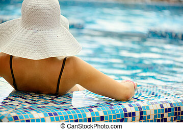 Beautiful girl in white hat relaxing at swimming pool