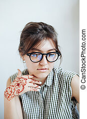 Beautiful girl in white room, with mehendi on a hand