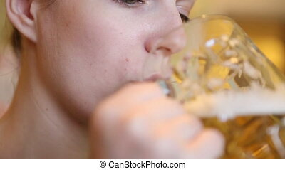 beautiful girl is drinking a large glass of beer