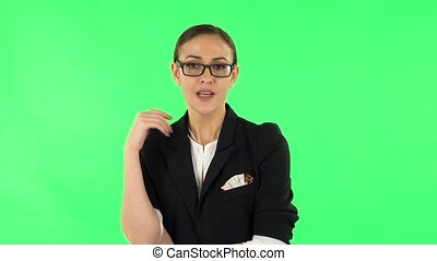 Beautiful girl is reporting and tells a lot of interesting informations. Girl with dark hair and glasses wearing a black business suit at green screen at studio.