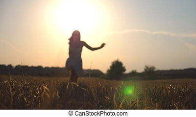 Beautiful girl is running along wheat field at sunset. Young woman jogging at the meadow and enjoing freedom. Summer leisure at nature concept. Close up Slow motion