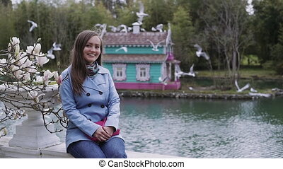 Beautiful girl is sitting on a background of a multi-colored bird house on the pond. Gulls fly away from the roof of the house