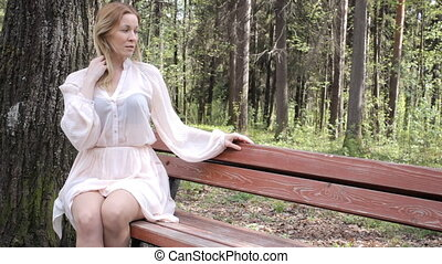Beautiful Girl is sitting on the bench in a park and smiling