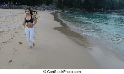 Beautiful girl jogging on the sandy beach - Aerial drone...