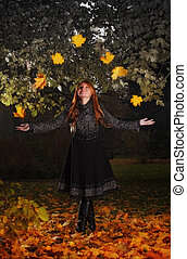 girl juggling leaves in autumn park