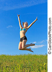 beautiful girl jumping against the blue sky