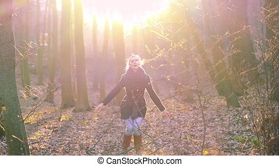 Beautiful girl jumping in a sunny spring forest. Slowly