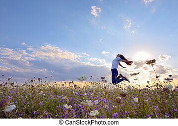 Beautiful girl jumping on summer field