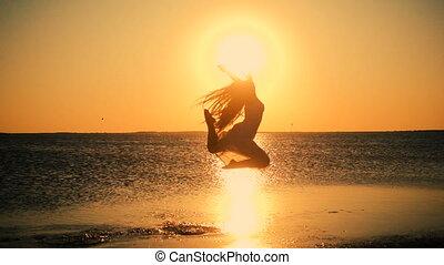 Beautiful girl jumping on the lake coast at sunset,...