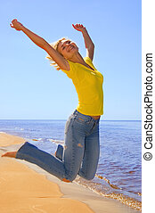 Beautiful girl jumps on a beach