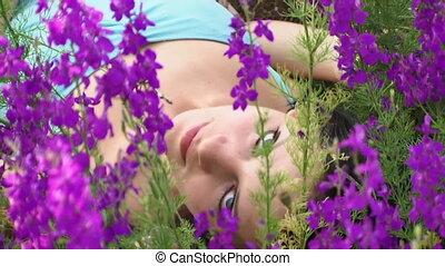 Beautiful girl lies among lupine