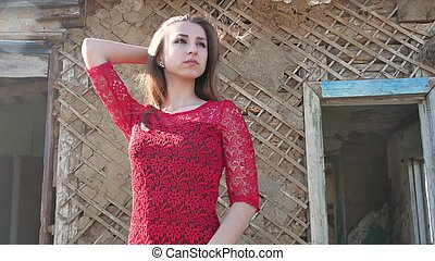Beautiful girl lifestyle in a red dress. Sexy girl in a dress is standing next to the old house of the ruins