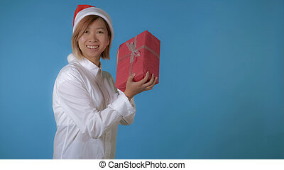 beautiful girl like santa holding red box with present