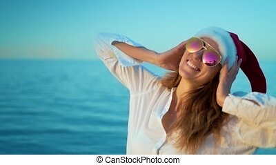 Beautiful girl listening to music on the phone at the sea in a Santa Claus hat, wearing sunglasses, wearing a white swimsuit and white headphones, a background of sea blue water.