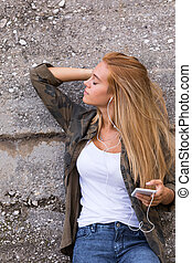 beautiful girl listening to music outdoors