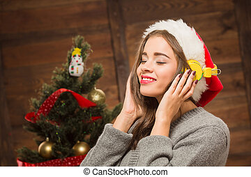 Beautiful girl listening to the music in front of New Year tree