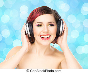 Beautiful girl listening to the music throughout headphones.