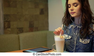 Beautiful girl listens to music in a cafe