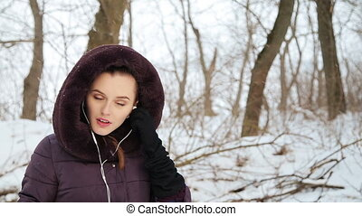 Beautiful girl listens to music in winter
