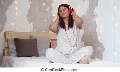 Beautiful girl listens to music on headphones in red and dances using phone