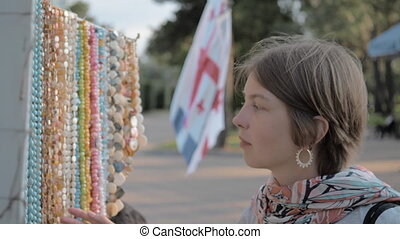 Beautiful girl looking at beads in the park of Batume, Georgia