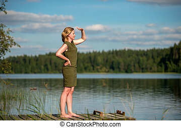 Beautiful girl looking into the distance standing on a wooden jetty at a lake