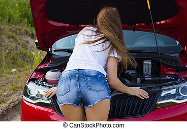 Beautiful girl looks at the engine under the hood of the car