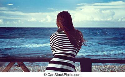 beautiful girl looks at the sea