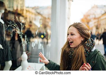 Beautiful girl looks at the shop window.