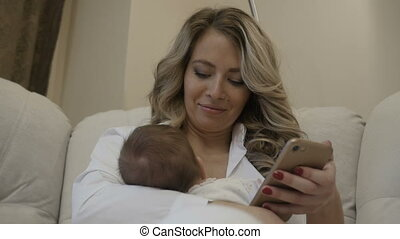 Beautiful girl looks in the phone with the baby on her hands
