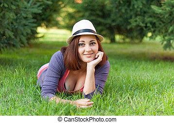 Beautiful girl lying in the green grass.