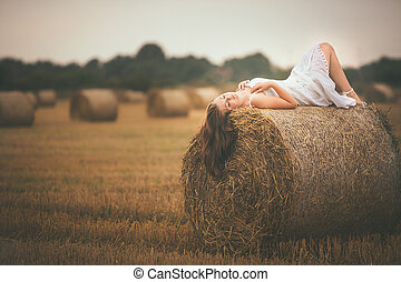 Beautiful Girl Lying on a Bale of Hay in the Field -...