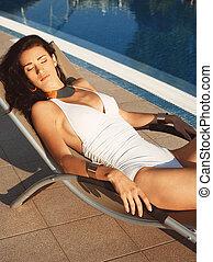Beautiful girl lying on a sun lounger