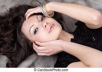 Beautiful girl lying on grey fur coat