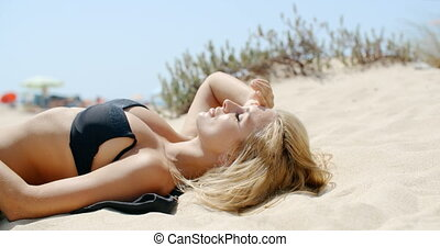 Beautiful Girl Lying on Sandy Dune and Taking Sunbath on...