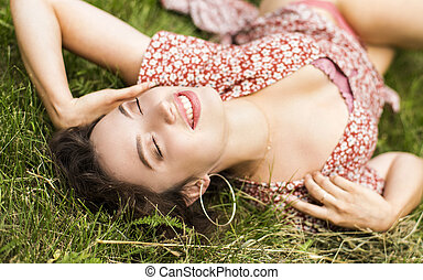 Beautiful Girl lying on the Field. Green Grass. Happy and Smiling