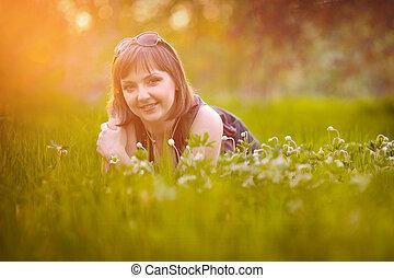 Beautiful girl lying on the grass in the sun
