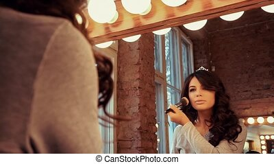 Beautiful girl makes a make-up before a mirror