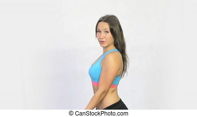 Beautiful girl makes exercise with dumbbells