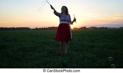 beautiful girl makes soap bubbles at sunset