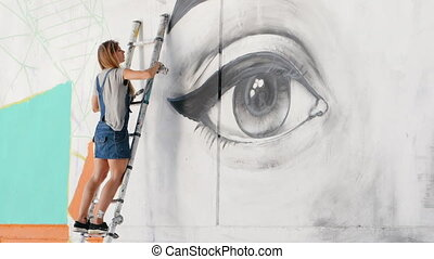 Beautiful girl making graffiti of big female face with...