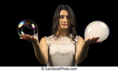 Beautiful girl making soap bubbles with smoke