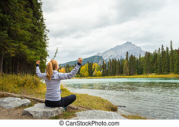 Beautiful girl meditating in the mountains