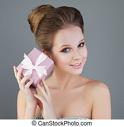Beautiful Girl Model and Pink Gift. Young Perfect Woman with Evening Makeup and Fashion Hairstyle