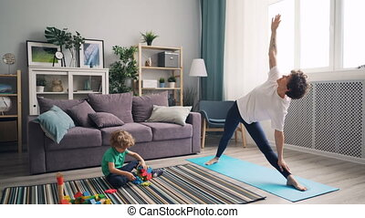 Beautiful girl mother doing yoga when kid playing with toys...