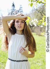 Beautiful girl near a flowering tree