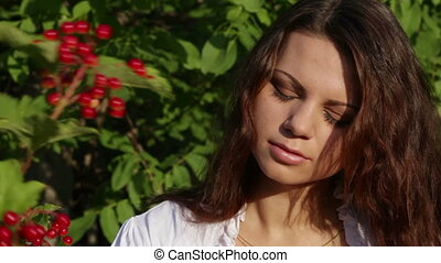 Beautiful girl near the bushes of viburnum and smiling