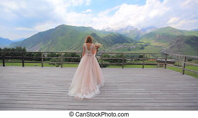 Beautiful girl on a background of a mountain landscape. Wedding day